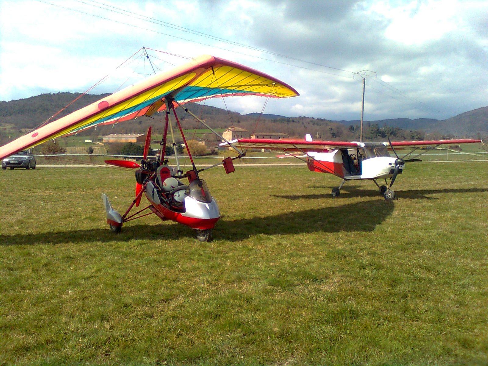 Photographie d'un appareil ULM pendulaire garé à côté d'un appareil ULM multiaxe sur la piste de Deyras lors de la journée des femmes de l'air.